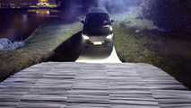Range Rover driving over a paper bridge