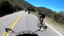 Cyclist passes motorcycles on mountain road