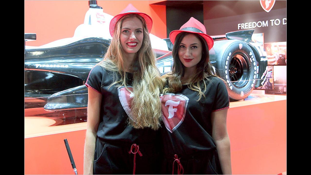 Ein behütetes Duo mit einem Formel-Wagen. Aber da passt doch immer nur eine rein? Oder hat der einen Beifahrerinnensitz?
