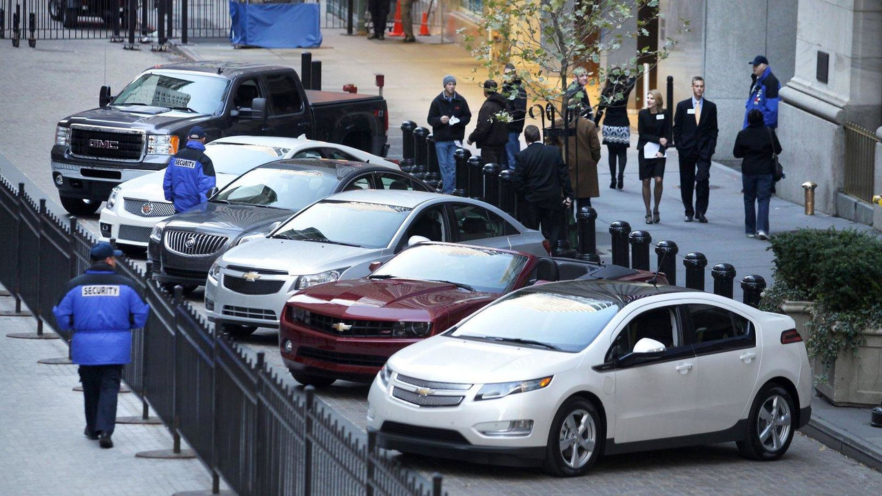 Passersby look on as General Motors' vehicles are displayed in front of the New York Stock Exchange on the morning of GM's initial public offering Thursday, November 18, 2010 in New York. (Photo by Todd Plitt for General Motors) 11/18/2010